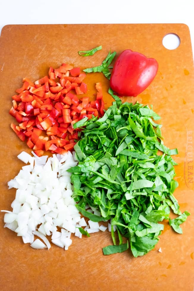 diced red bell pepper, onion, and spinach on brown cutting board