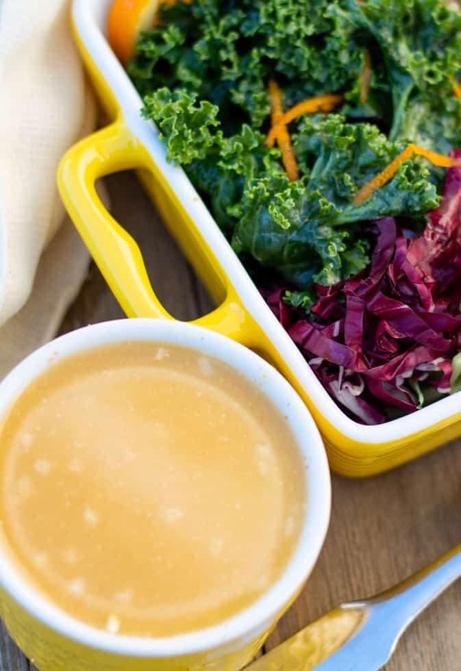 orange citrus salad dressing in yellow bowl beside kale salad