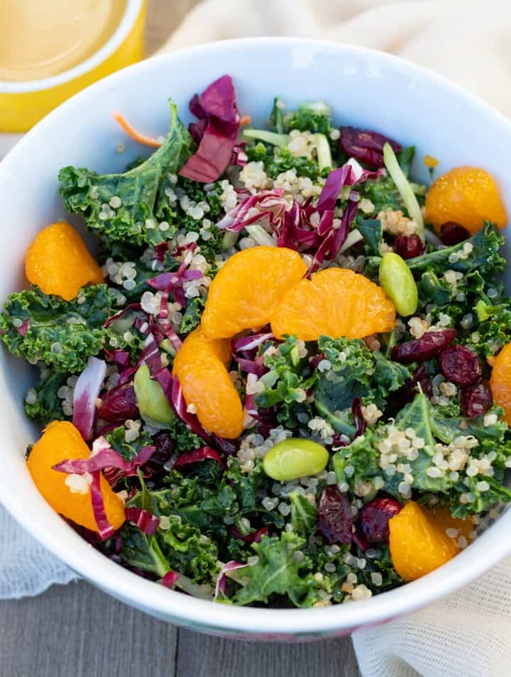 kale salad with quinoa and orange slices in white bowl