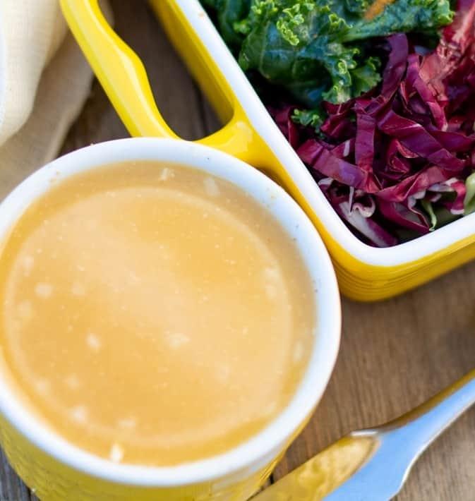 orange citrus salad dressing in yellow bowl beside kale salad