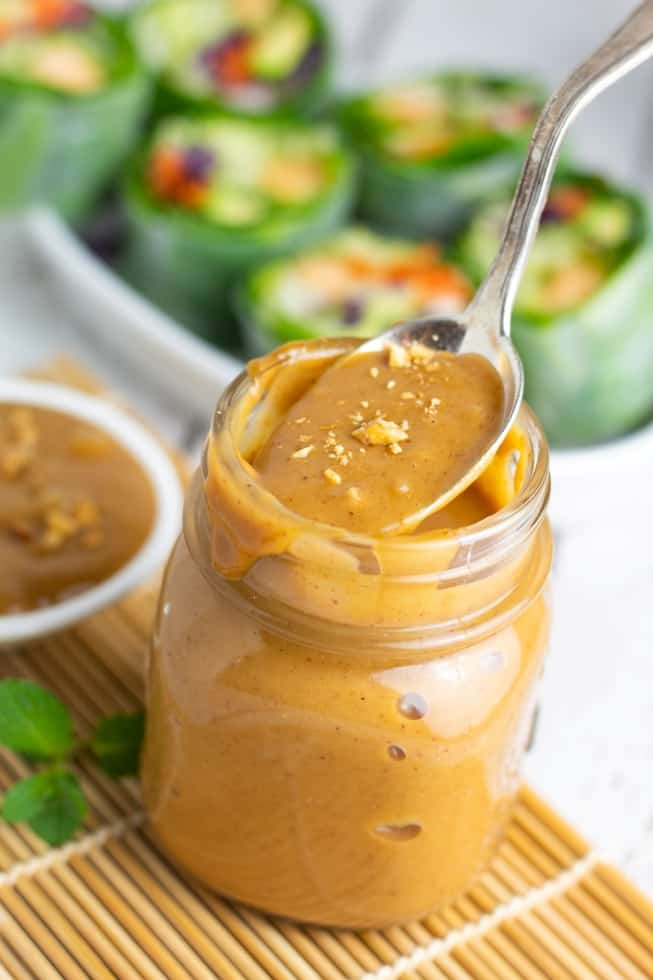 peanut sauce in jar with spoon with spring rolls in background