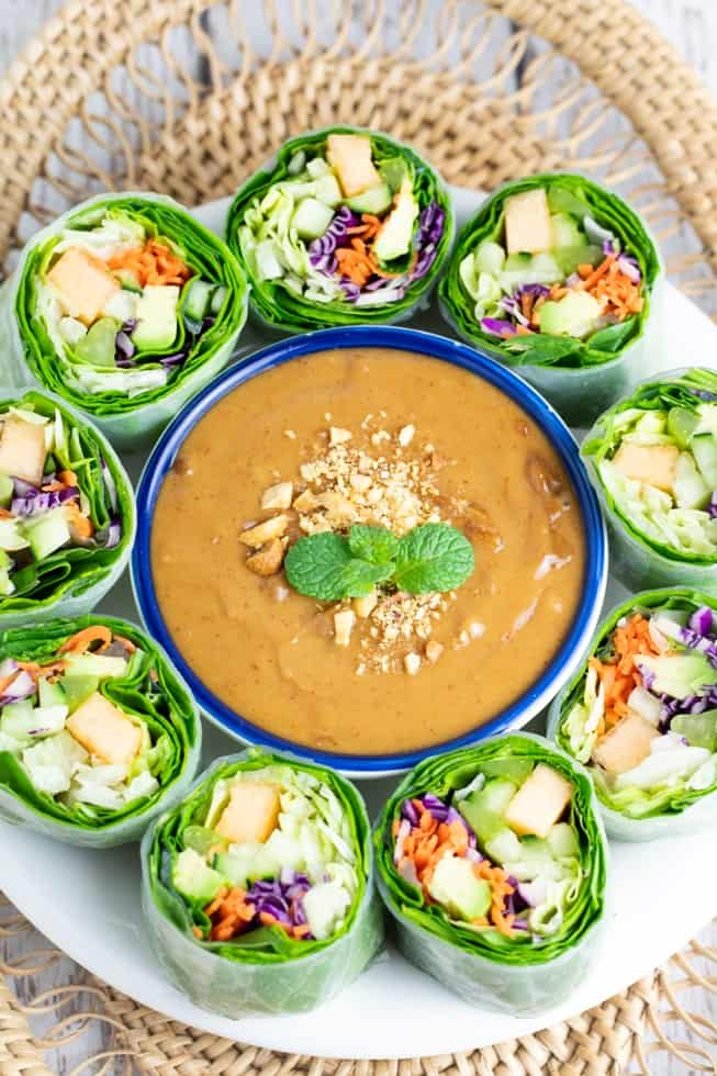 overhead of peanut sauce on platter surrounded by spring rolls
