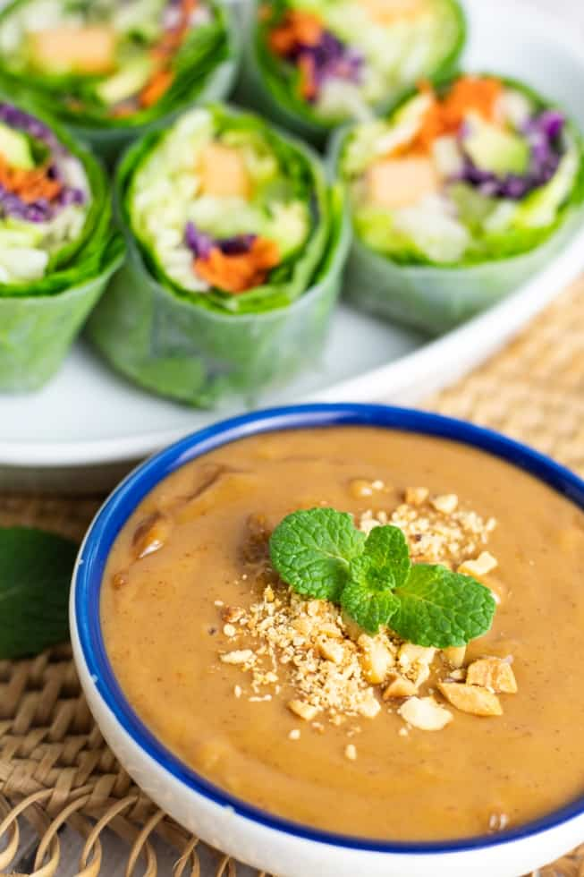 peanut sauce in blue bowl with spring rolls in background