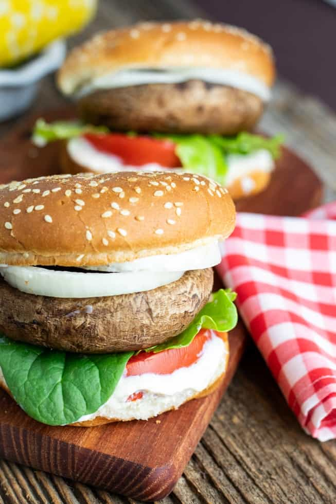portobello mushroom burgers on brown cutting board with red checkered napkin