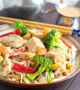 rice noodle veggie stir fry on brown plate with chop sticks