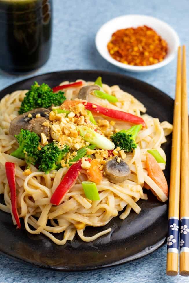 vegetable noodle stir fry on black plate with chopsticks