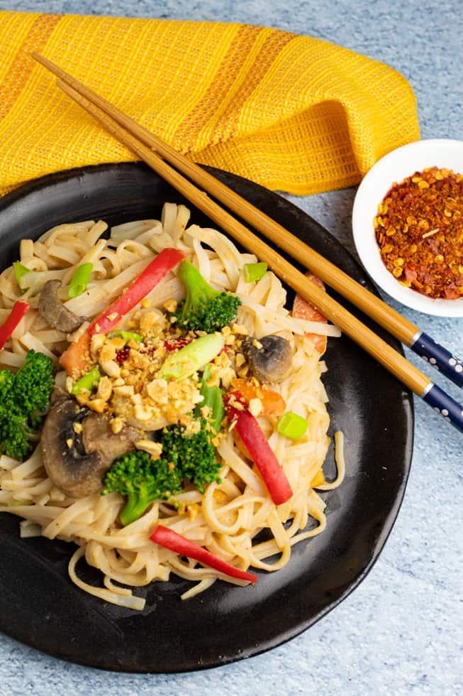 vegetable noodle stir fry on black plate with chopsticks and orange napkin