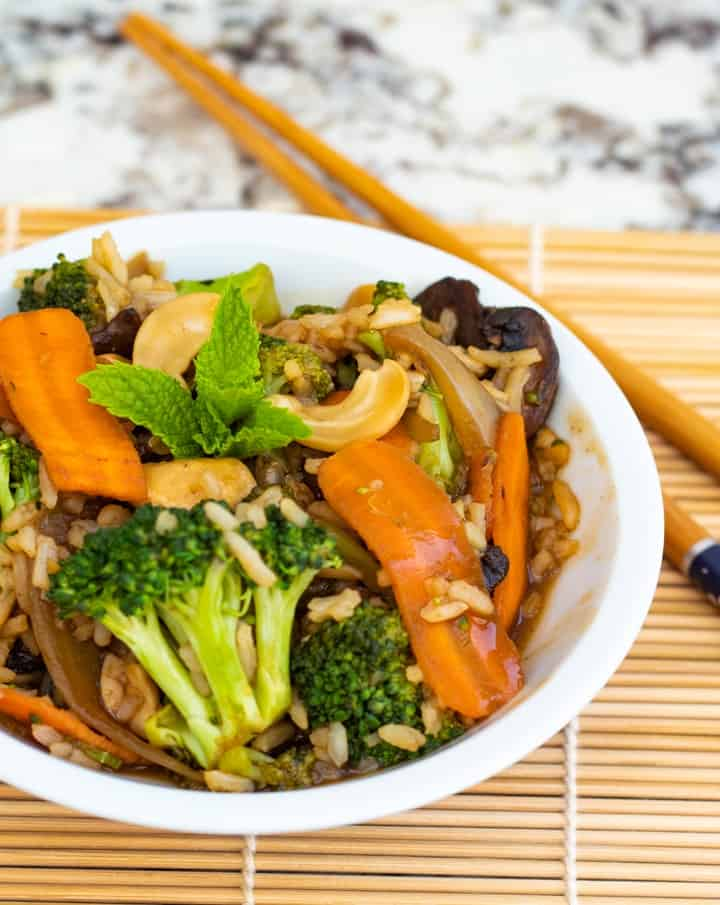 chinese vegetable stir fry in white bowl with chopsticks