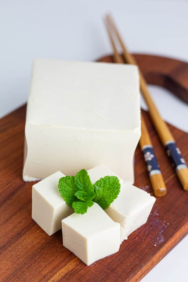 block of tofu with three chunks in front and mint leaf, chopstick on side