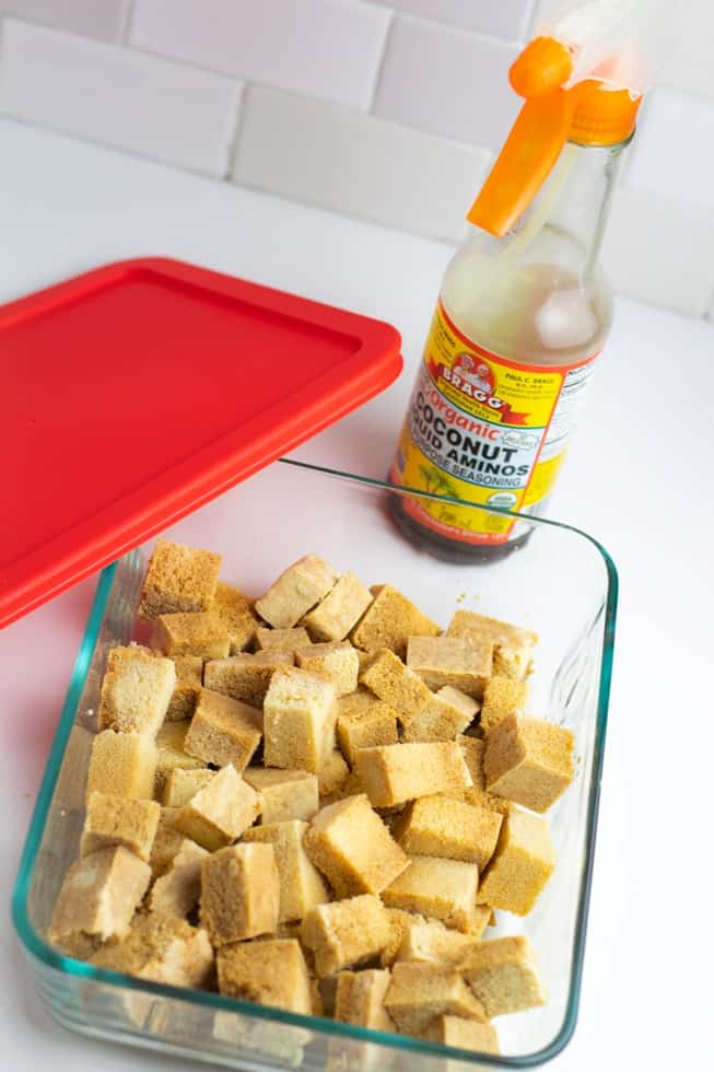 tofu marinating in glass dish with bottle of coconut aminos in background