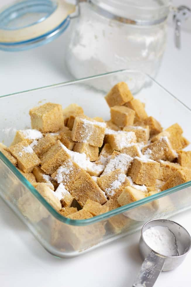 tofu cubes in glass dish covered with spices and cornstarch