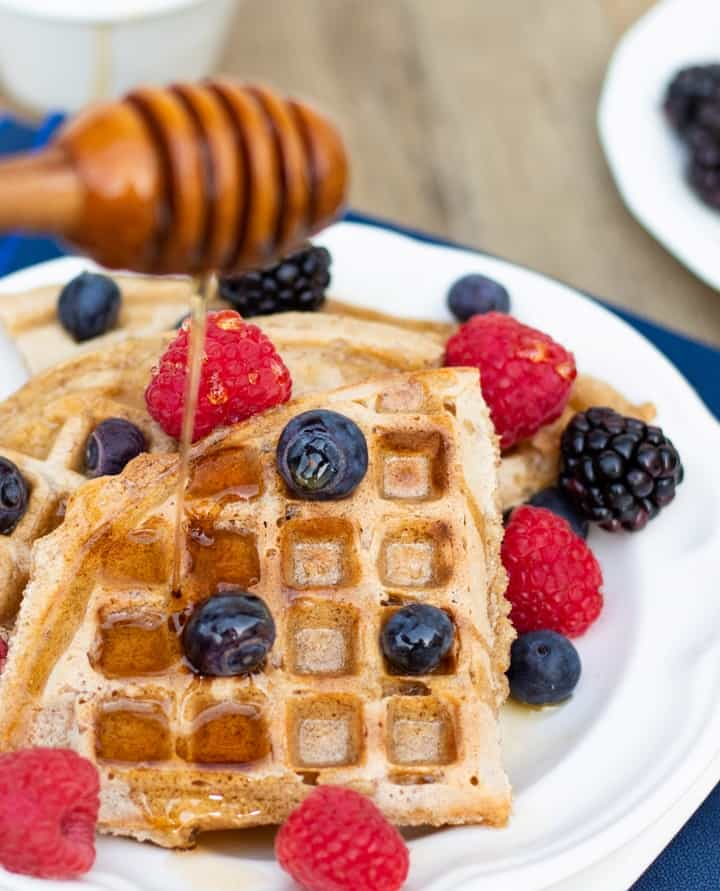 gluten free waffles with blueberries and raspberries and maple syrup being drizzled over top