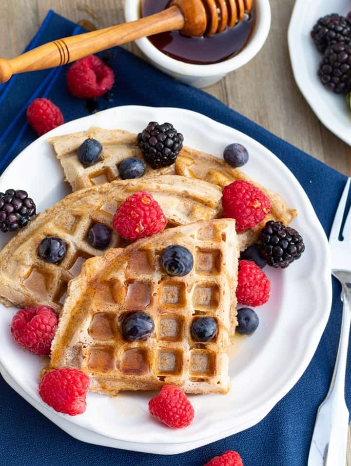 vegan waffles cut into triangles with fruit overhead shot