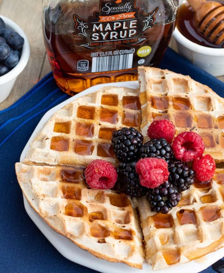 round vegean waffles topped with blackberries raspberries, and maple syrup