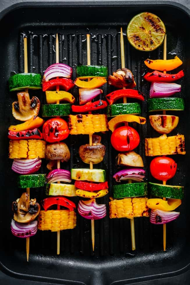 veggie kabobs with corn, purple onion, tomato, and peppers on black pan