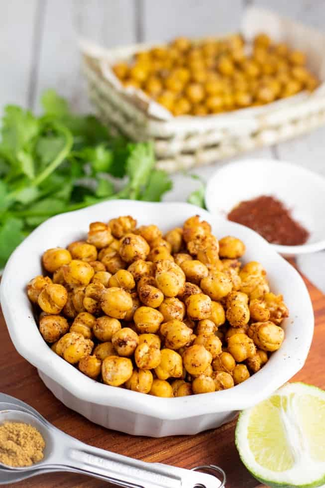 roasted chickpeas in white bowl with basked of chickpeas in background
