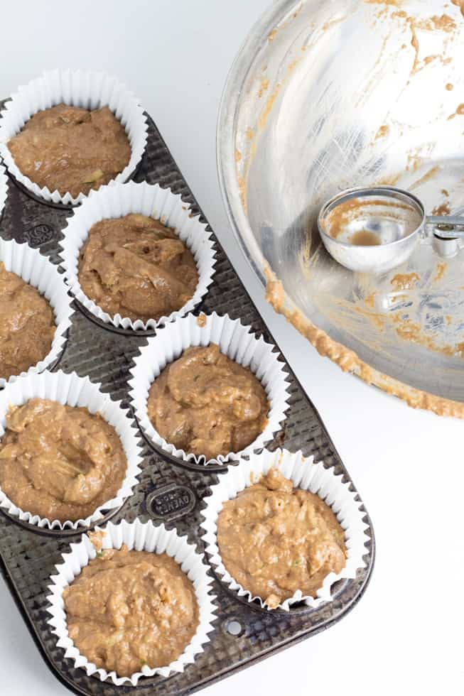 vegan chocolate muffins in old metal muffin tin with empty batter bowl with ice cream scoop