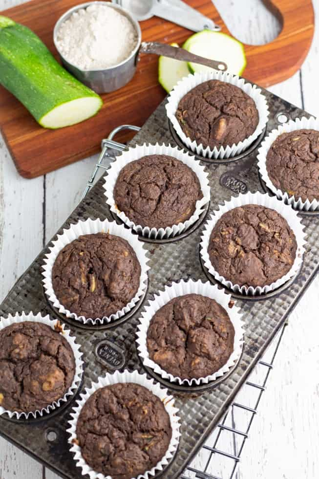vegan chocolate zucchini muffins in white muffin paper cups in metal muffin pan on cooling rack zucchini in background