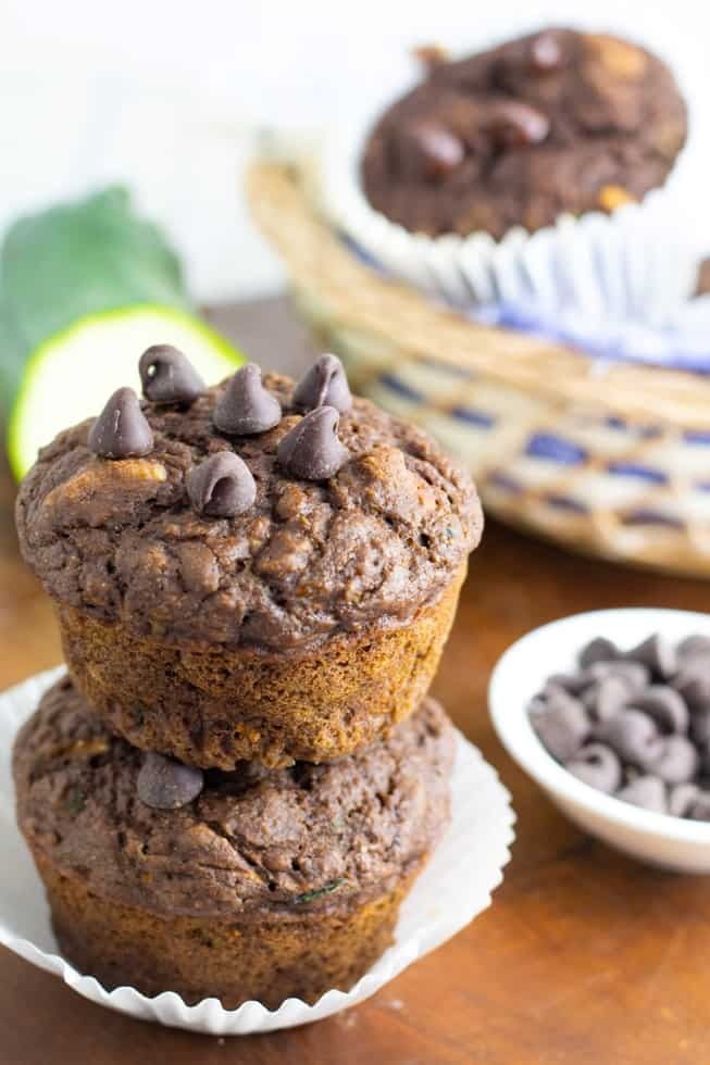 chocolate zucchini vegan muffins two stacked with chocolate chips in background