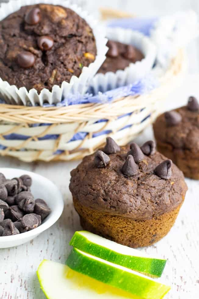vegan chocolate muffins with slices of zucchini and basketfull of muffins in background