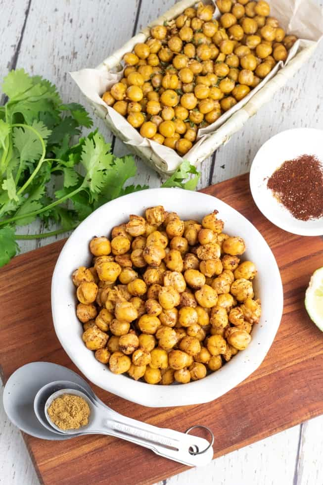 crispy roasted chickpeas in white bowl and basket with meassuring spoon and spices