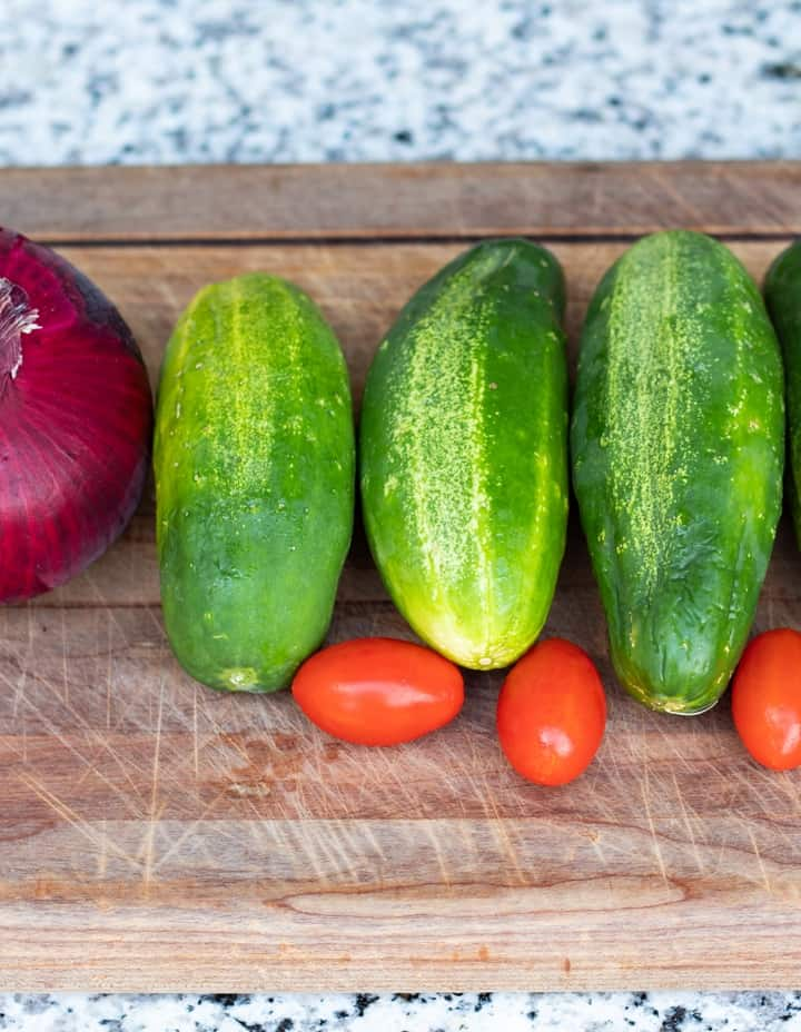 four cucumbers, cherry tomatoes, and red onion on wood cutting board