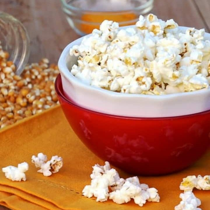 air popped corn in red bowl with popped kernels around