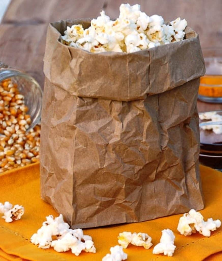 popcorn in brown paper back with kernels on napkin in front