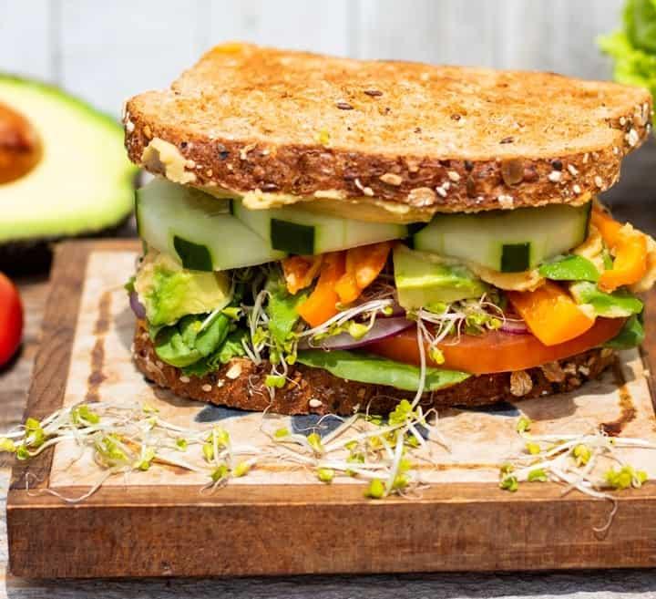 hummus sandwich with veggies on wood block