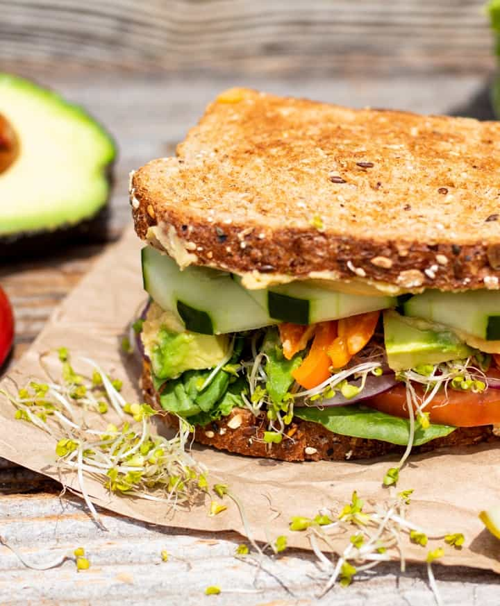 hummus sandwich with veggies on brown paper with avocado in background