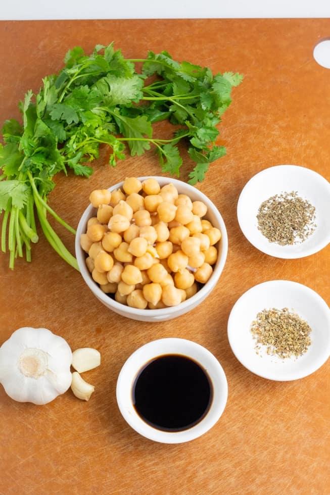 cilantro, chickpeas, balsamic vinegar, garlic clove, and spices on brown cutting board
