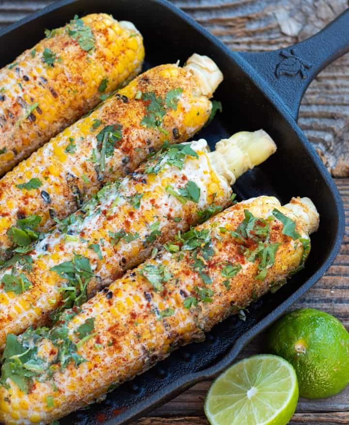 Mexican corn in black cast iron pan with lime wedge