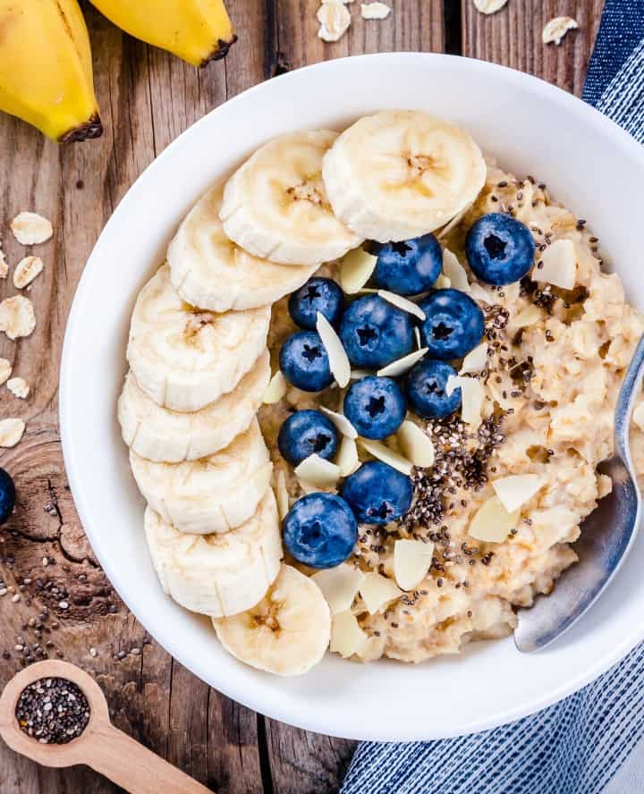 overnight oatmeal in white bowl topped with banana and blueberries with spoon in bowl