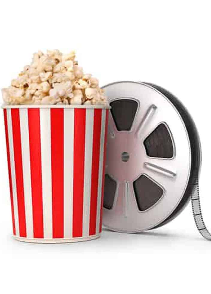 movie popcorn in red and white striped container with movie reel beside