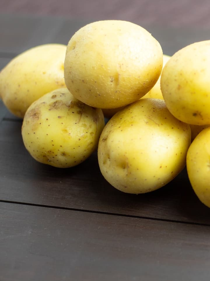 whole yellow potatoes on wooden board