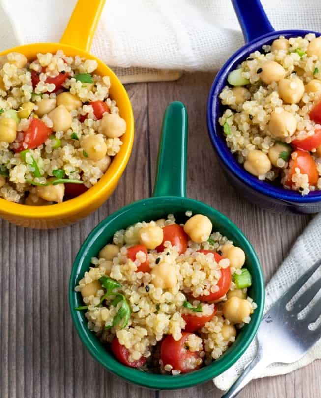 overhead shot of quinoa chickpea salad in 3 colorful bowls blue, green, yellow