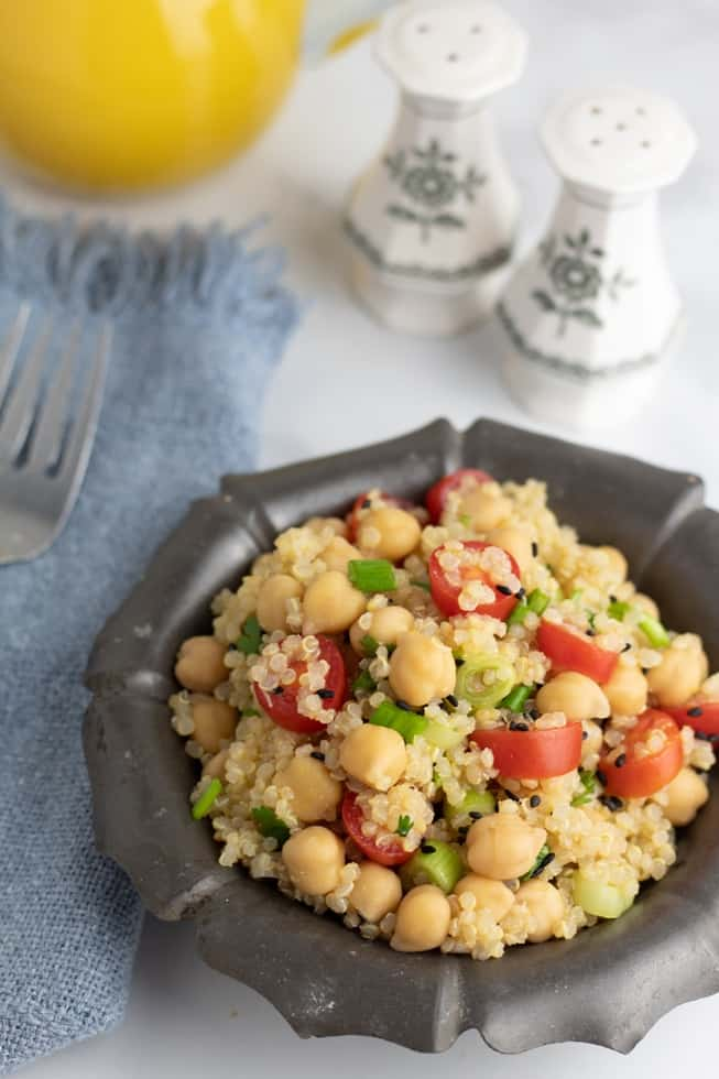 quinoa chickpea salad in gray bowl with salt shakers in background