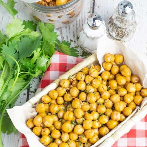 overhead photo of basket full of chickpea snack on red checkered napkin and cilantro