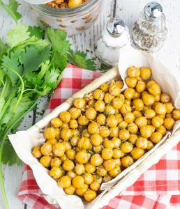 basket full of chickpea snack on red checkered napkin and cilantro