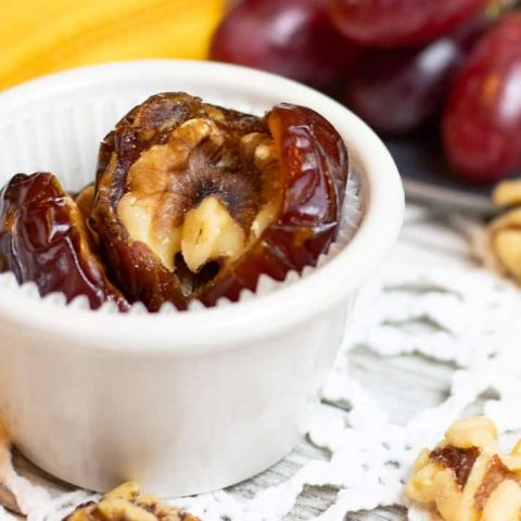 dates stuffed with walnuts in white bowl on lace tabletop