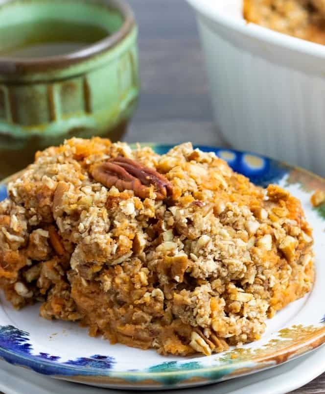 serving of sweet potato casserole on colorful plate with coffee cup in background