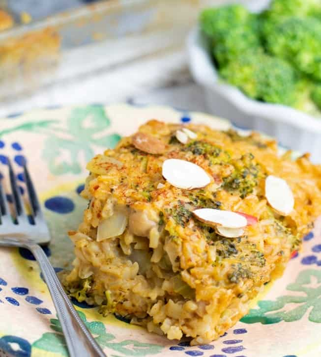 vegan broccoli casserole serving on colorful plate with casserole dish in background