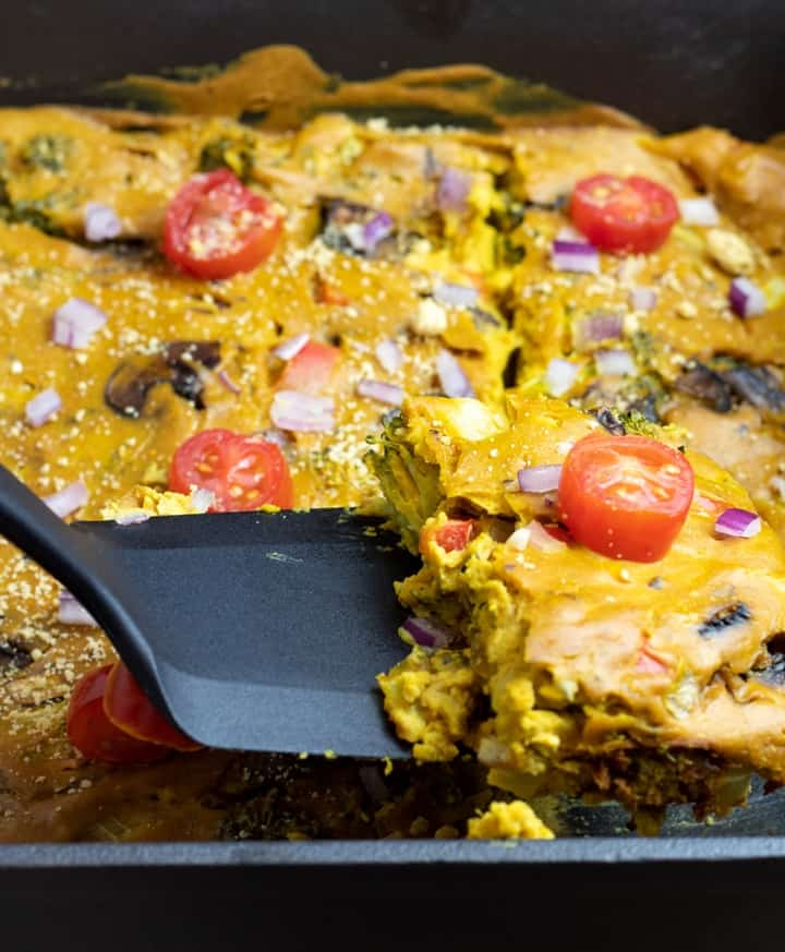Vegan Quiche being lifted with black spatula from cast iron