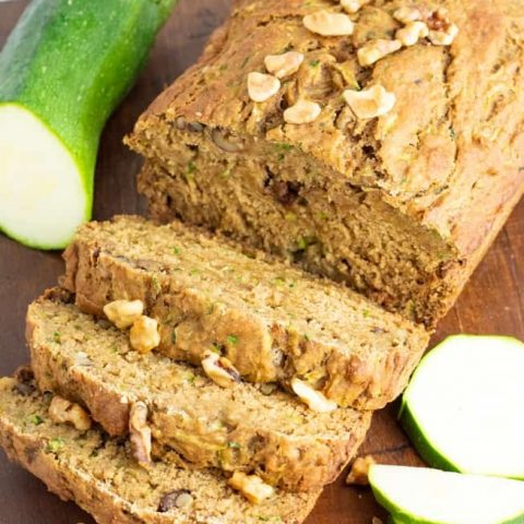 close up of sliced vegan zucchini bread on wooden board with zucchini beside