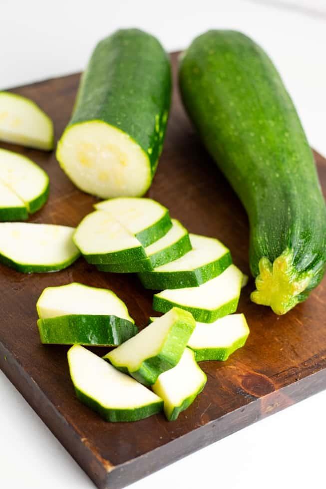 zucchini whole and sliced on dark wood cutting board