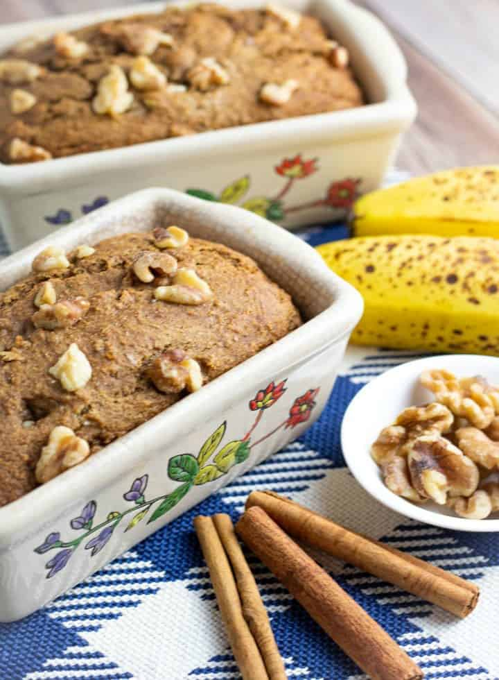 2 small loaves of banana bread with cinnamons sticks, walnuts, and banana in background