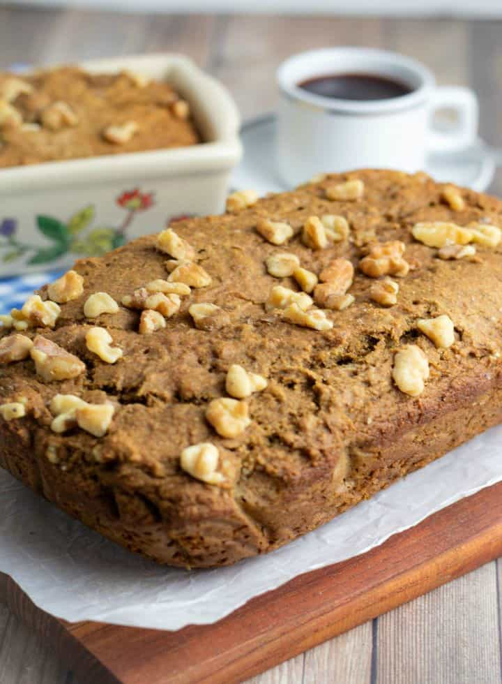 loave of banana bread on cutting board with cup of coffee in background