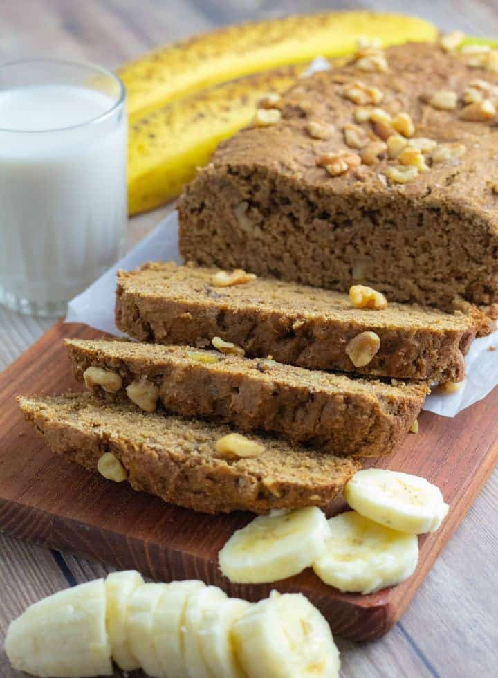 loaf of vegan banana bread sliced on cutting board with slices of banana and glass of milk
