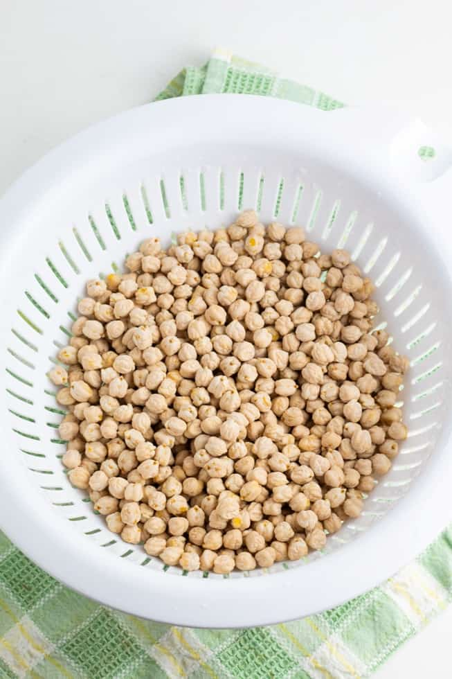 raw chickpeas being rinsed in white colander