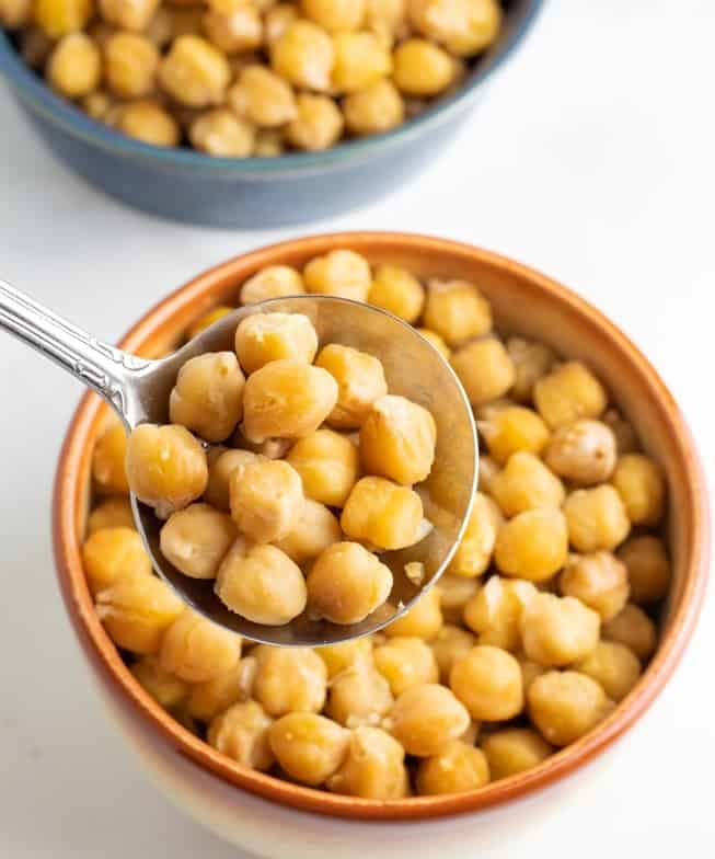 close up of cooked chickpeas in spoon over brown bowl on white background
